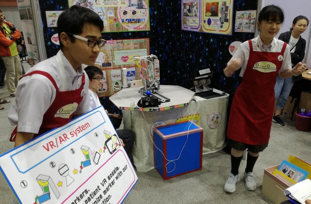 世界大会でロボットの仕組みなどについて説明する中学チーム(追手門学院大手前中学・高校の福田哲也教頭提供)