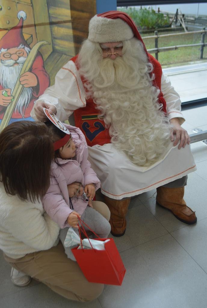 子供たちにプレゼントを手渡すサンタクロース。西日本豪雨被災地の子供たちを励まそうと、フィンランドの北極圏サンタ村から来日した=関西国際空港(谷田智恒撮影)