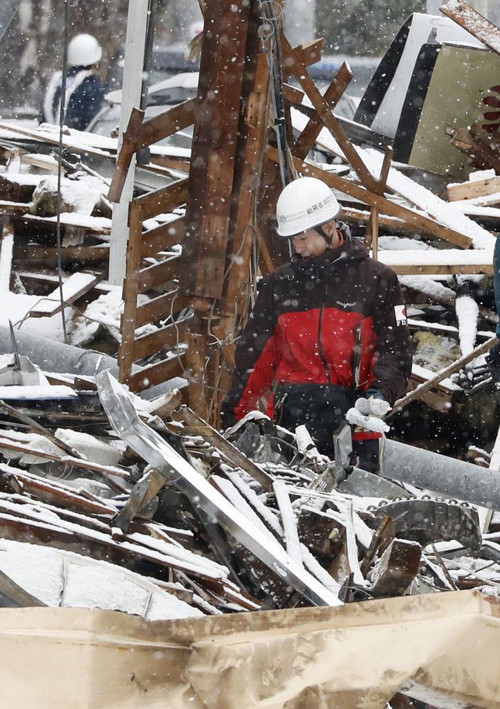 爆発のあった現場付近を調べる総務省消防庁の職員=18日午前、札幌市豊平区