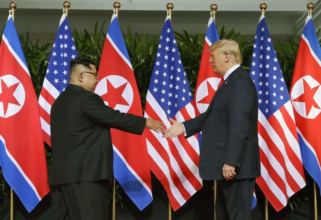 会談の冒頭で握手を交わす北朝鮮の金正恩朝鮮労働党委員長(左)とドナルド・トランプ米大統領=6月12日、シンガポール(AP)