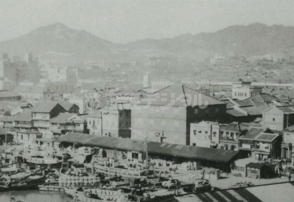 昭和10年ごろの神戸の海岸通り。中央の大きな建物の西隣に陳舜臣の実家「三色の家」が写っている(神戸市文書館提供)