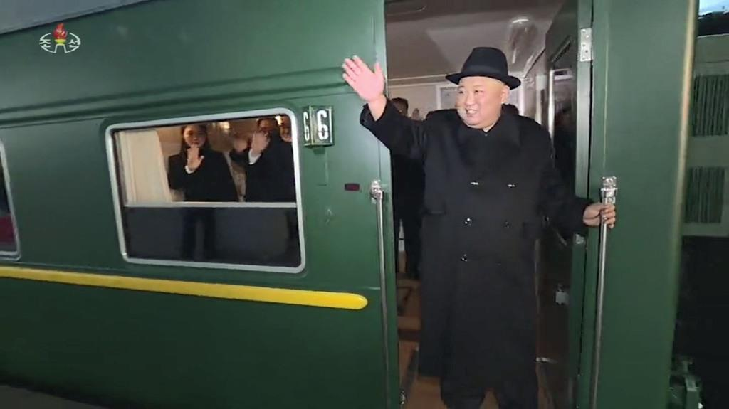 7日、訪中のため平壌で列車に乗り込み手を振る北朝鮮の金正恩朝鮮労働党委員長の映像。朝鮮中央テレビが8日放映した(共同)