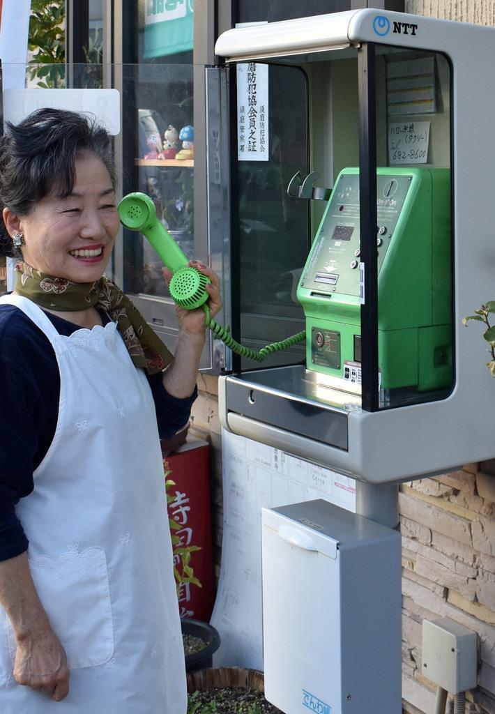 阪神大震災直後から使い続けている喫茶店前の公衆電話を手にする岡本美治さん=神戸市須磨区