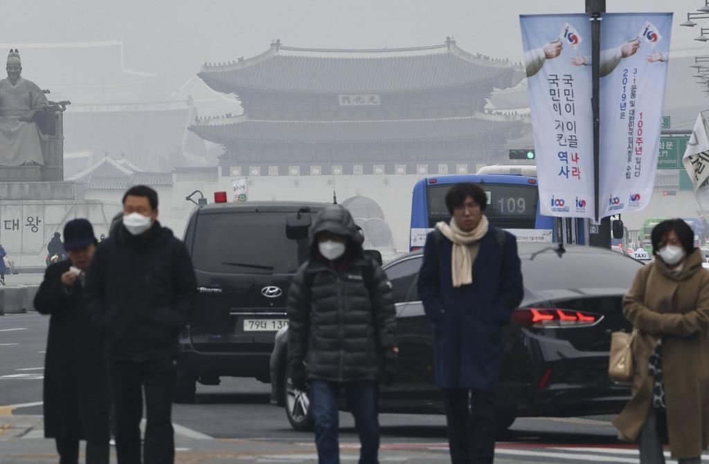 大気汚染で白っぽくかすんだソウル中心街を歩くマスク姿の人々=14日(共同)