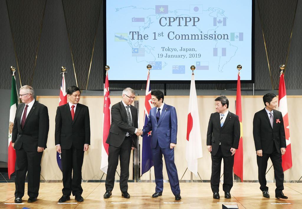 記念撮影後、TPP参加国の閣僚らと握手する安倍首相(右から3人目)=19日午後、東京都内のホテル