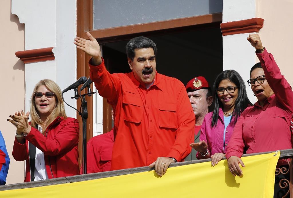 23日、ベネズエラ大統領府のバルコニーから支持者に手を振るマドゥロ大統領(中央)=カラカス(AP)