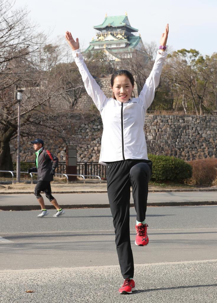 大阪城を背景にグリコの看板のポーズをとる招待選手の何引麗(ホー・インリ)=25日午前、大阪市中央区(鳥越瑞絵撮影)