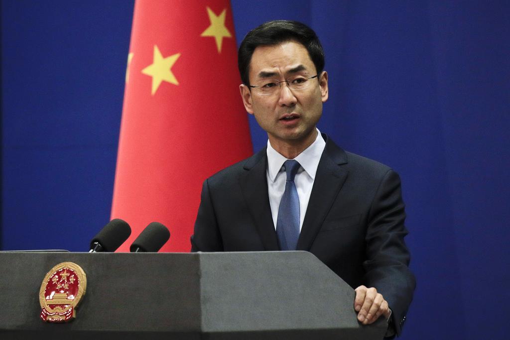 会見する中国外務省の耿爽報道官=29日、北京(AP)