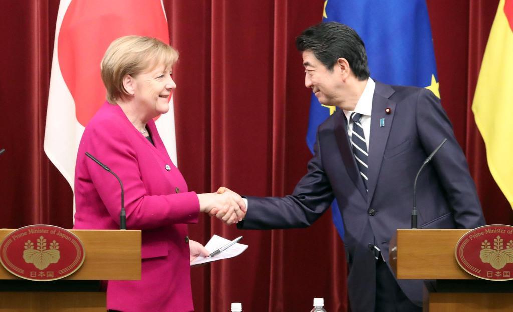 日独共同記者会見を終え握手を交わすドイツ・メルケル首相(左)と安倍晋三首相=4日午後、首相官邸(春名中撮影)