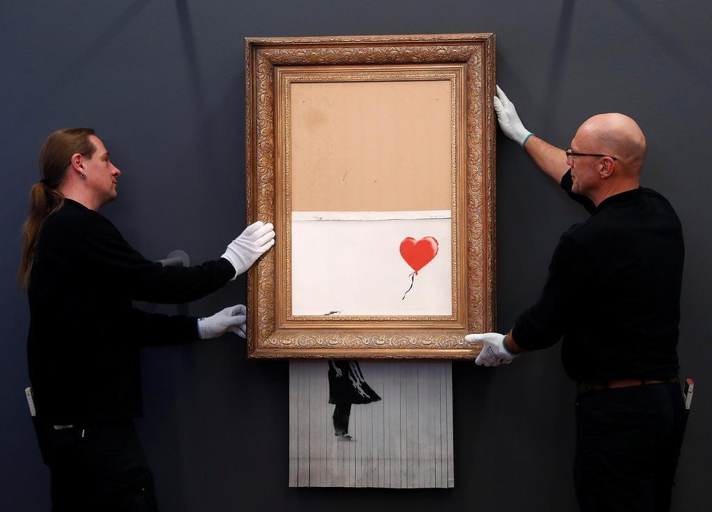 ドイツのバーデンバーデンで、バンクシーの細断作品を展示場所に設置する美術館員=4日(ロイター)