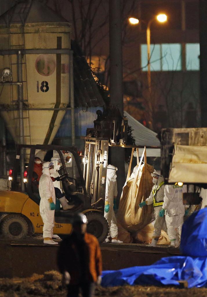 豚コレラの感染が確認された愛知県豊田市の養豚場で、日没後も続けられる防疫作業=6日午後6時16分