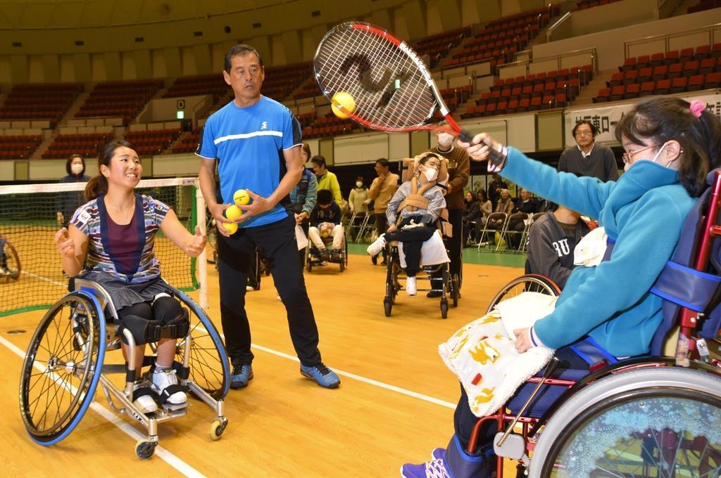 子供にボールの打ち方を指導する上地結衣選手(左)=神戸市中央区