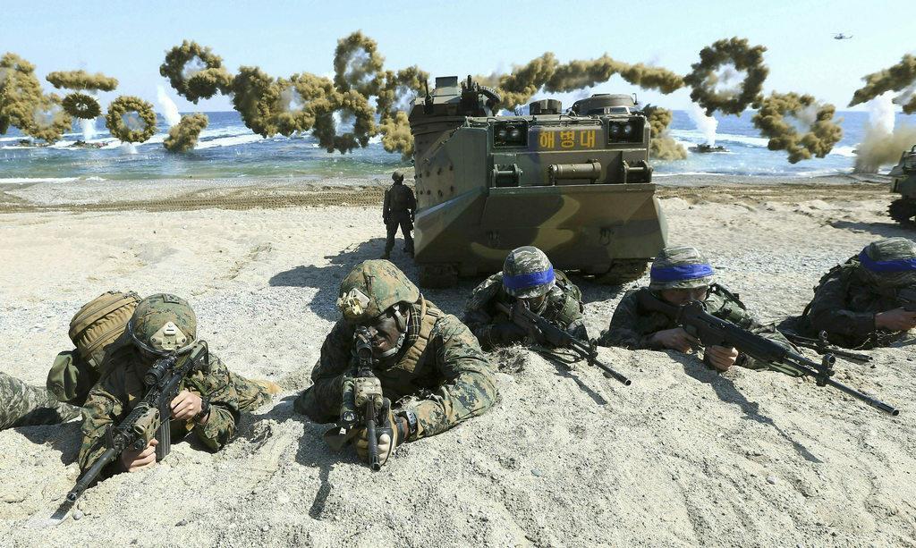 米韓合同軍事演習「キー・リゾルブ」「フォールイーグル」の一環として実施された「双竜」と名付けられた上陸訓練。左が米軍、ヘルメットに青い帯をつけているのが韓国軍兵士=2016年3月、韓国の浦項(AP)