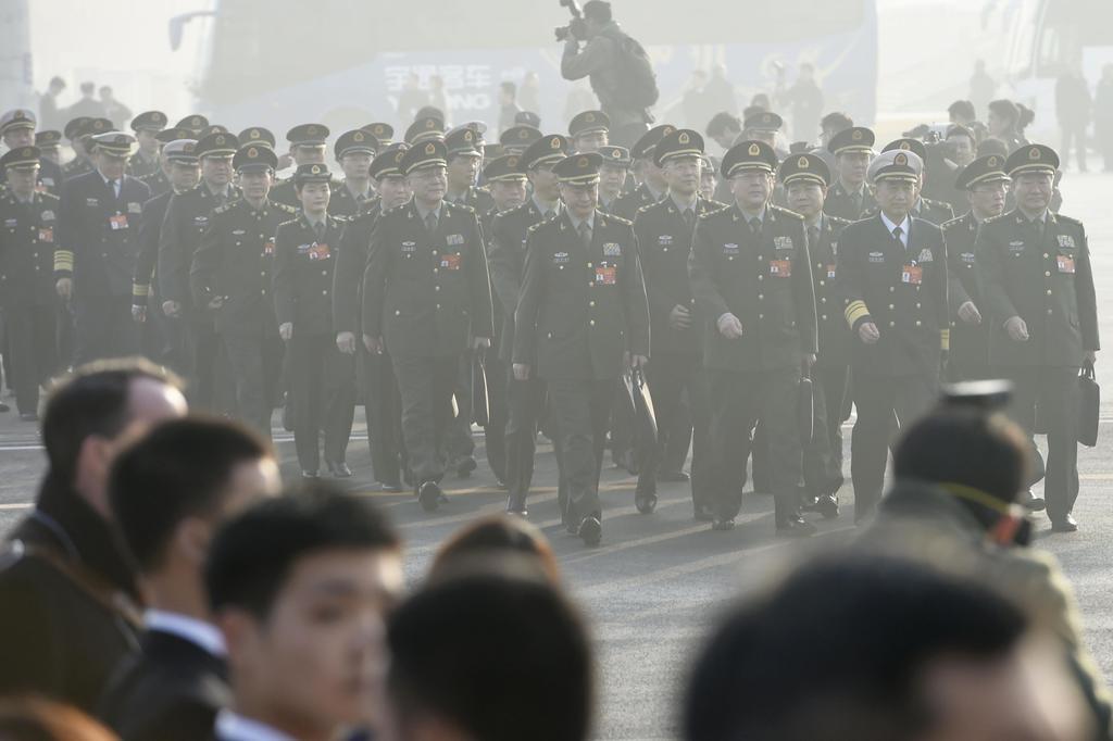 北京の人民大会堂に向かう中国全人代の人民解放軍の代表ら。深刻な大気汚染で遠方がかすむ=5日(共同)