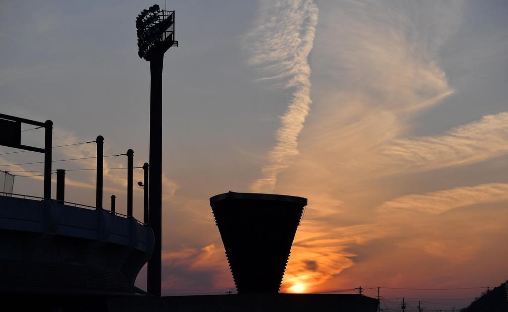 石巻市総合運動公園に設置された本物の聖火台。日没で照らされた雲が、聖火の煙のように空へ伸びた=2月22日午後、宮城県石巻市(納冨康撮影)