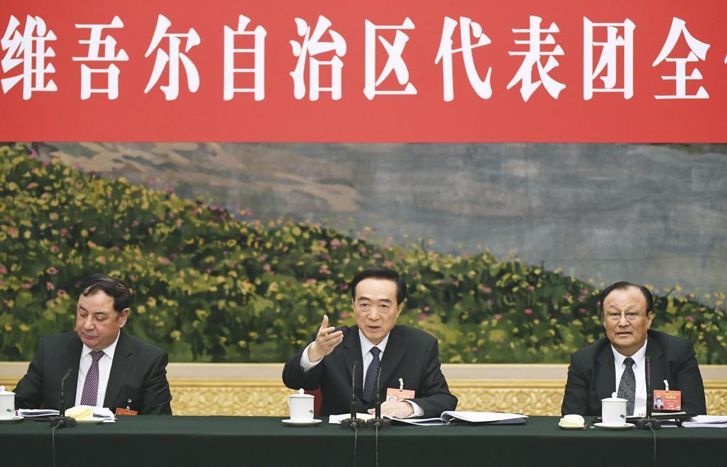全人代に合わせて開かれた新疆ウイグル自治区の会議に出席する陳全国・共産党委員会書記(中央)とショハラト・ザキル主席(右)=12日、北京の人民大会堂(共同)