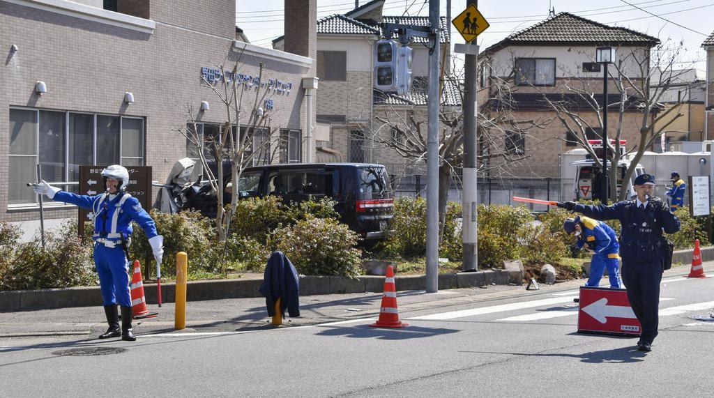 交差点で人をはね、施設の壁に衝突した車(中央奥)=13日午前11時24分、千葉県野田市