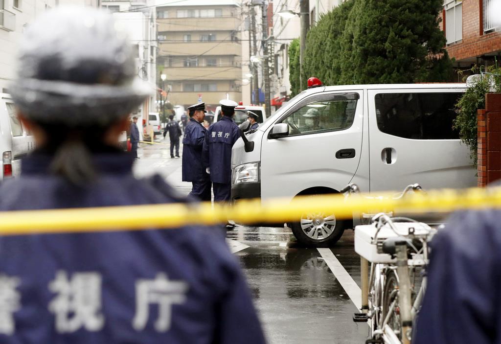 高齢女性が手足を縛られ死亡しているのが見つかった現場のマンション前で警戒にあたる警察官=2月28日午後、東京都江東区