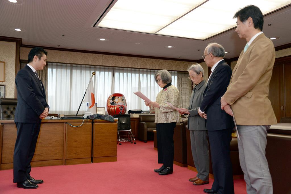 山下貴司法相(左)に死刑執行に関する詳細な情報開示を求める文書を手渡す高橋シズヱさん=13日午後、法務省