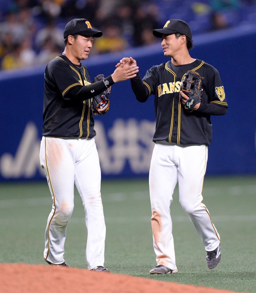 試合に勝利しタッチする阪神の大山悠輔(左)と木浪聖也=13日、ナゴヤドーム(水島啓輔撮影)