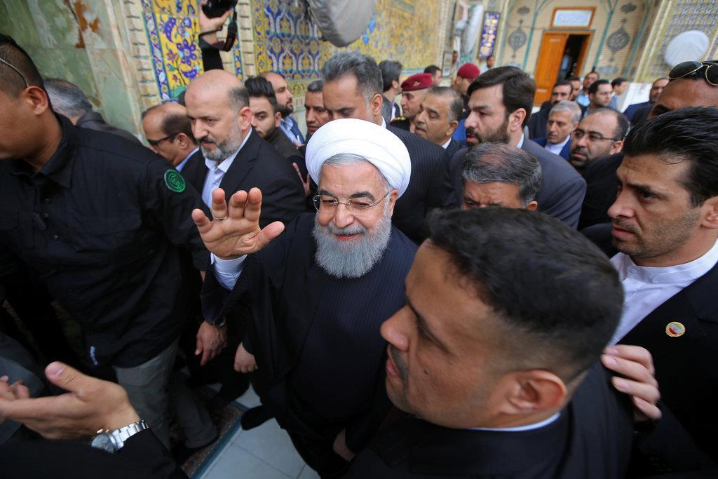 13日、シーア派で神聖視されるイラク中部ナジャフのイマーム・アリー廟を訪れるイランのロウハニ大統領(中央)=ロイター