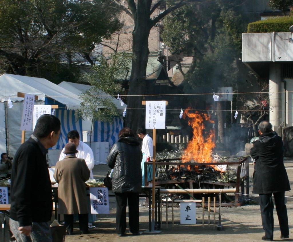 大阪天満宮のとんど神事。しめ縄飾りの分別が指示されている=大阪市北区