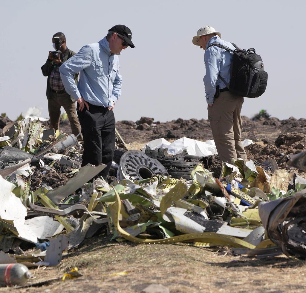 エチオピア航空機の墜落現場で機体の残骸を調査する米運輸安全委員会の当局者ら=12日、エチオピア・アディスアベバ郊外(ゲッティ=共同)