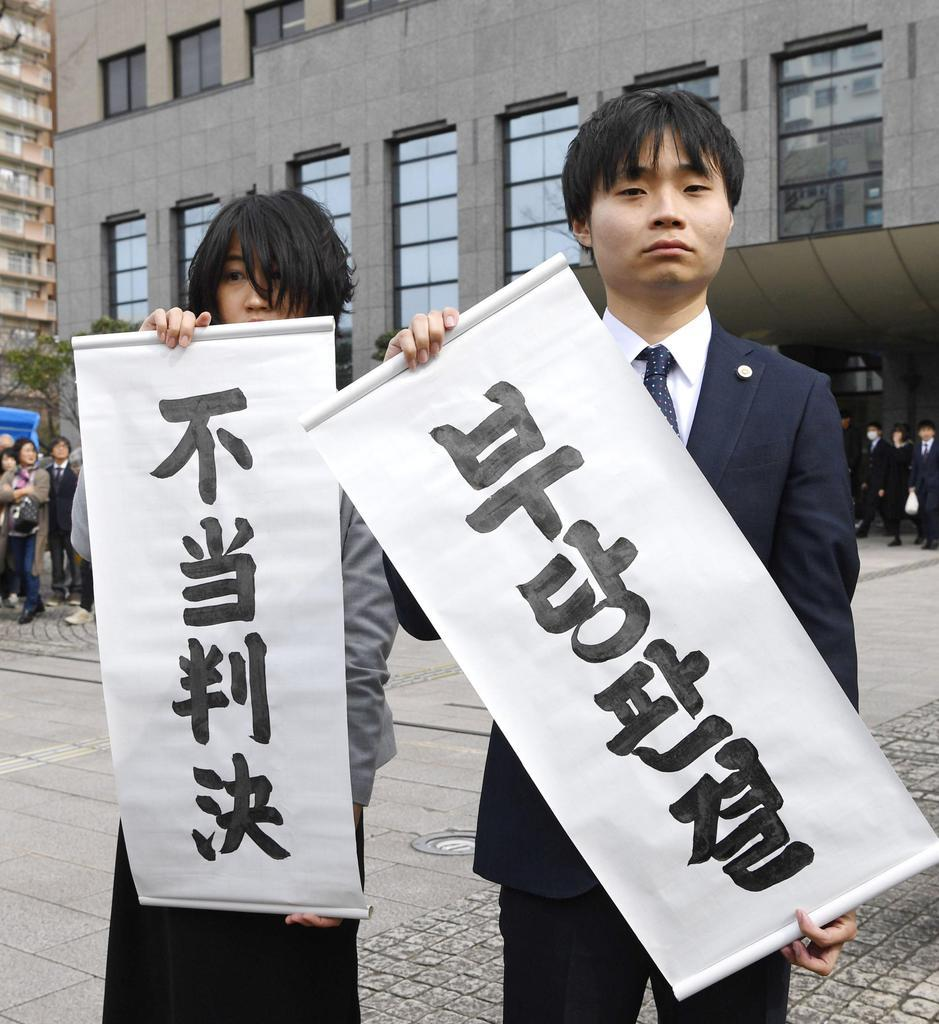 高校無償化を巡り九州朝鮮中高級学校の卒業生が国に損害賠償を求めた訴訟で、請求が棄却され「不当判決」の垂れ幕を掲げる原告側の弁護士=14日午後、福岡地裁小倉支部前