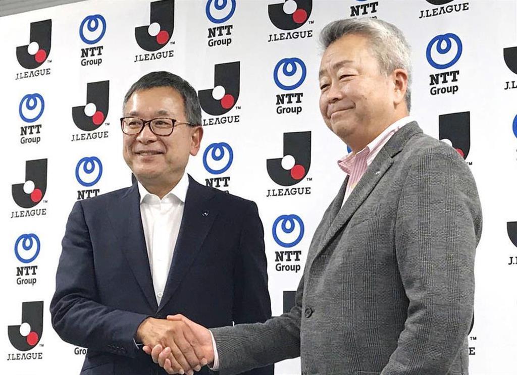 握手をするJリーグの村井満チェアマン(左)とNTTの澤田純社長=14日午後、東京都文京区