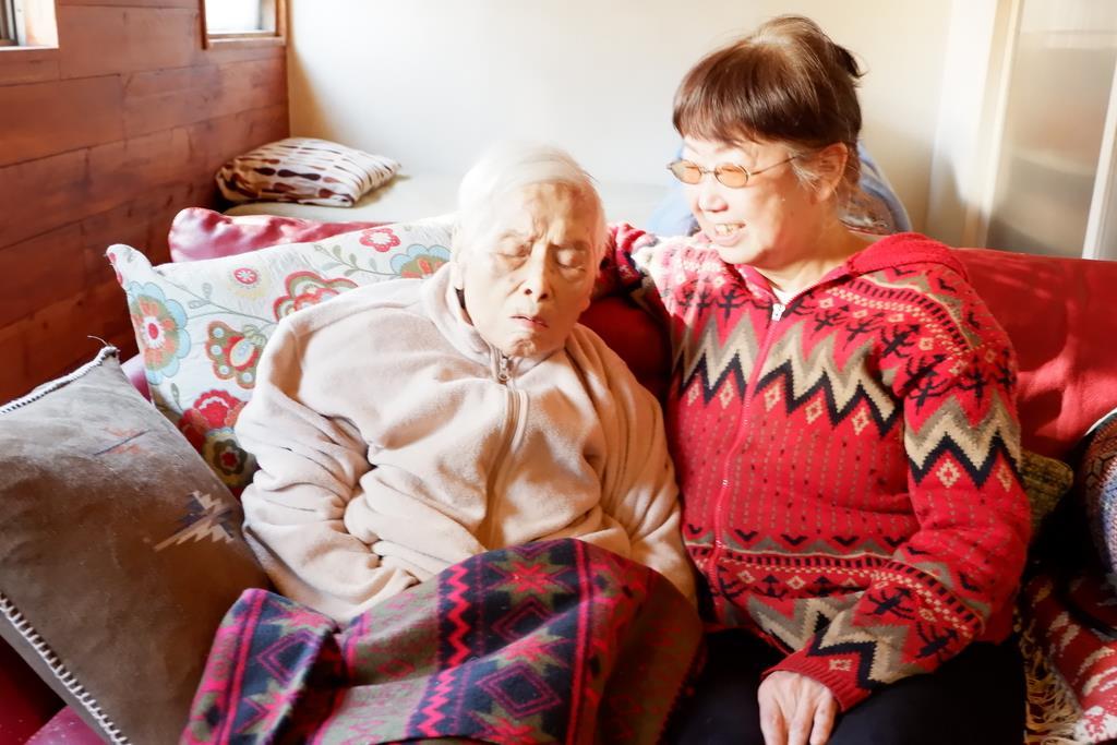 今年に入ってから入退院を繰り返すようになった酒井アサヨさん(左)と、「家にいるときは寝ている時間が増えた」と話す娘の章子さん=大阪市中央区