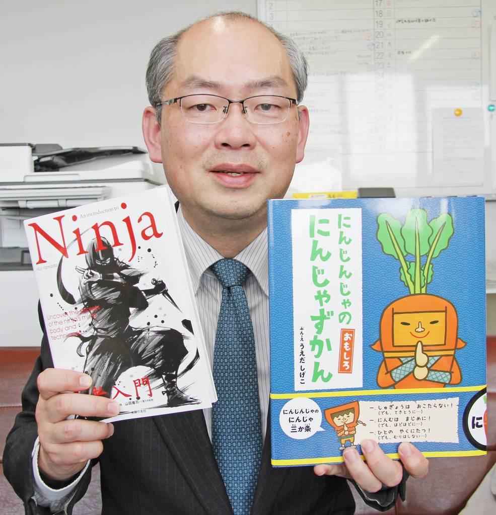 監修した2冊の本を手にする三重大の山田雄司教授