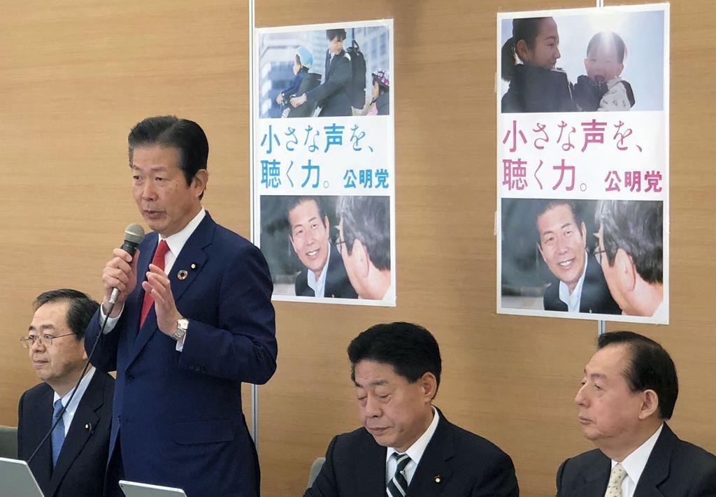 会合で新ポスターの狙いを説明する公明党の山口那津男代表(左から2人目)=14日、東京都内