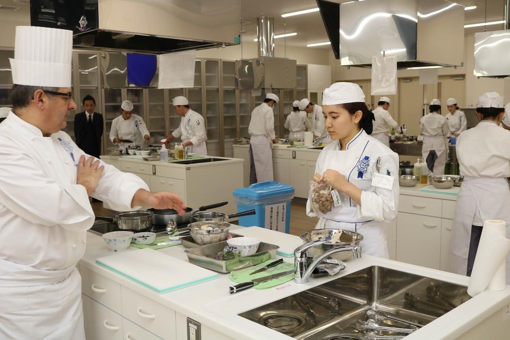 フランス人講師から調理指導を受ける学生=立命館大びわこ・くさつキャンパス