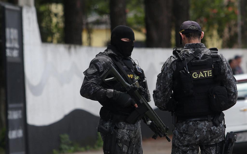乱射事件が発生した学校の前で警戒する警察官=13日、ブラジル・サンパウロ郊外(ロイター)