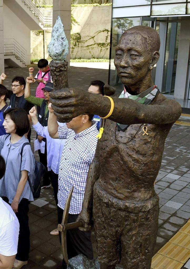 徴用工像のそばで気勢を上げる市民団体のメンバー=2018年7月、釜山(共同)