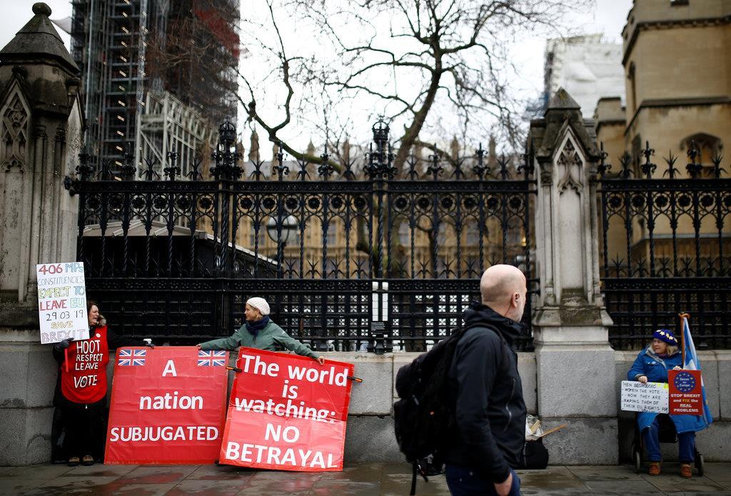 EU離脱賛成派と反対派がそれぞれプラカードを掲げる前を通り過ぎる男性=14日、英ロンドンの国会議事堂前(ロイター)
