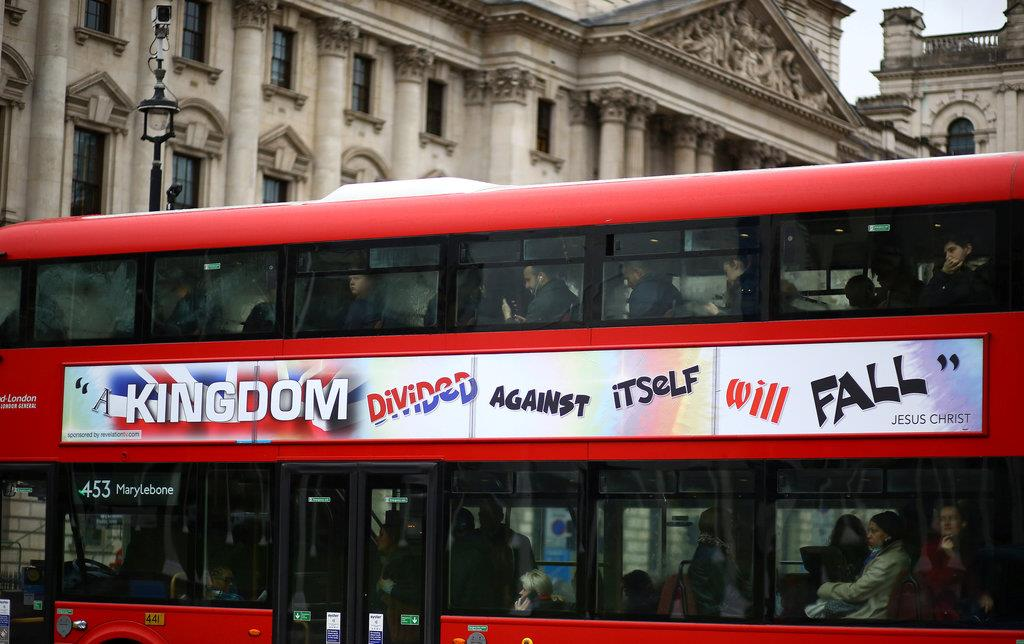 窓の外を見やる2階建てバスに乗った通勤客ら=14日、英ロンドンのウエストミンスター(ロイター)