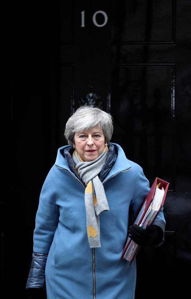 国会から外に出るテリーザ・メイ英首相=14日、英ロンドン(ロイター)