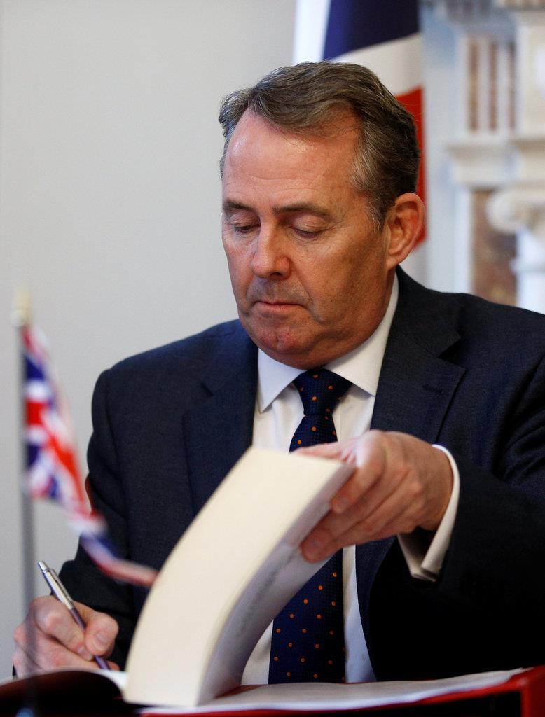 英がEUを離脱した際、太平洋諸国との貿易を継続する合意書にサインする英のリアム・フォックス国際貿易相=14日、英ロンドンの国会(ロイター)