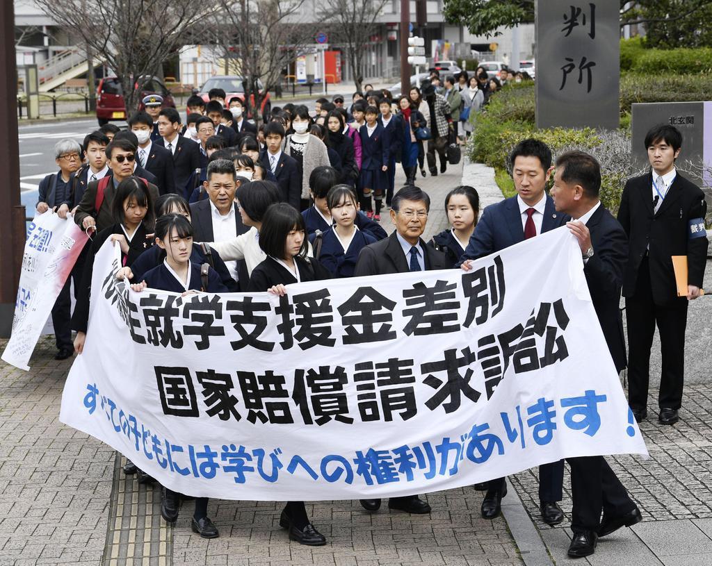 高校無償化を巡り九州朝鮮中高級学校の卒業生が国に損害賠償を求めた訴訟の判決を前に、福岡地裁小倉支部に入る原告団ら=14日午後
