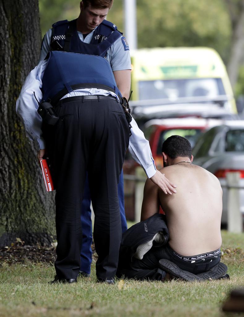 15日、ニュージーランド・クライストチャーチのモスクの外で座り込む男性に声をかける警官(AP)