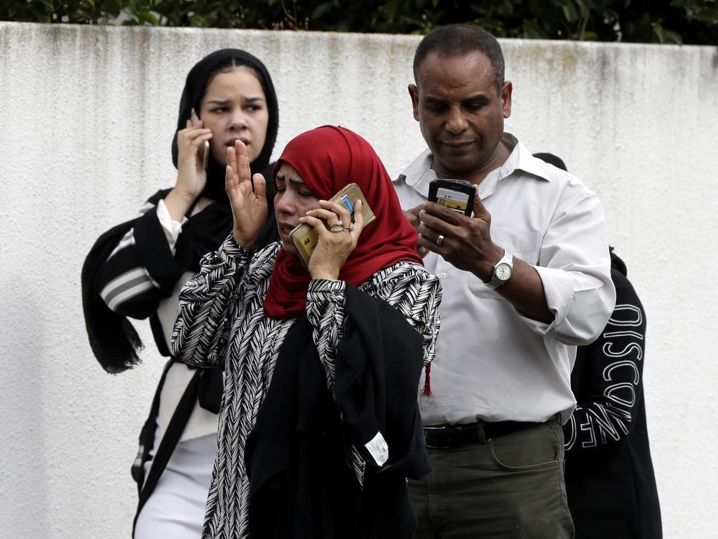 15日、ニュージーランド・クライストチャーチのモスクの外に立つ人たち(AP)