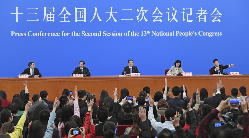 中国全人代が閉幕し、記者会見する李克強首相(中央)ら=15日、北京の人民大会堂(共同)