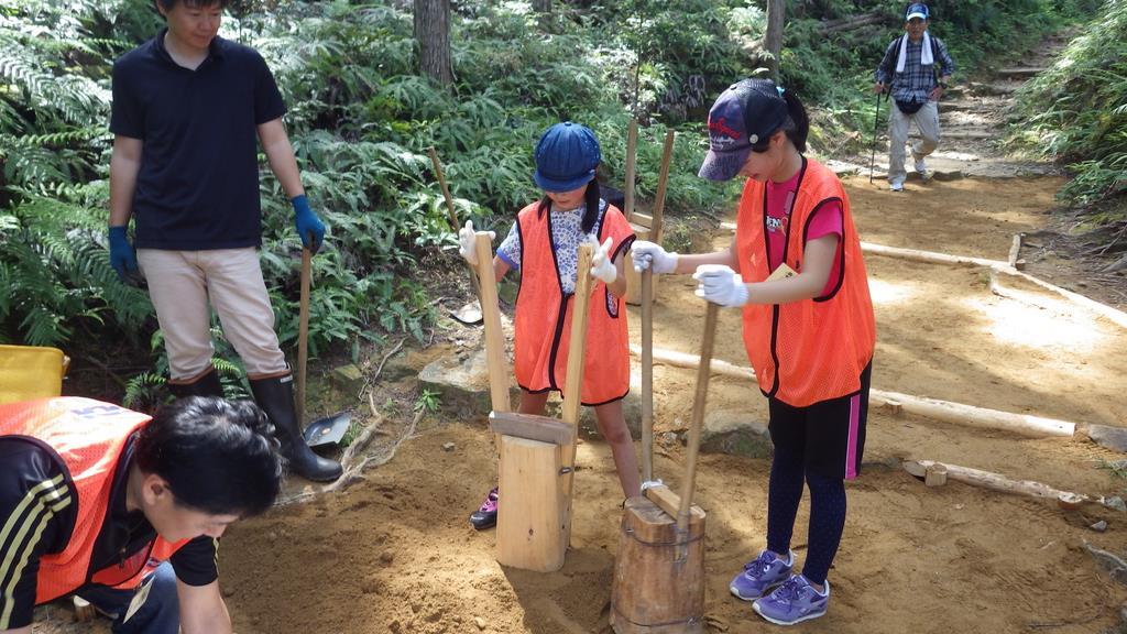 熊野古道で土を固める作業にあたる参加者ら=田辺市(県提供)
