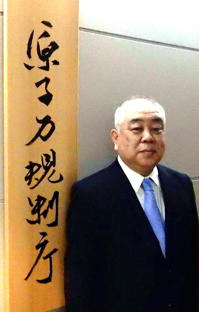 自らが筆を執った原子力規制庁の看板の前で =東京都港区