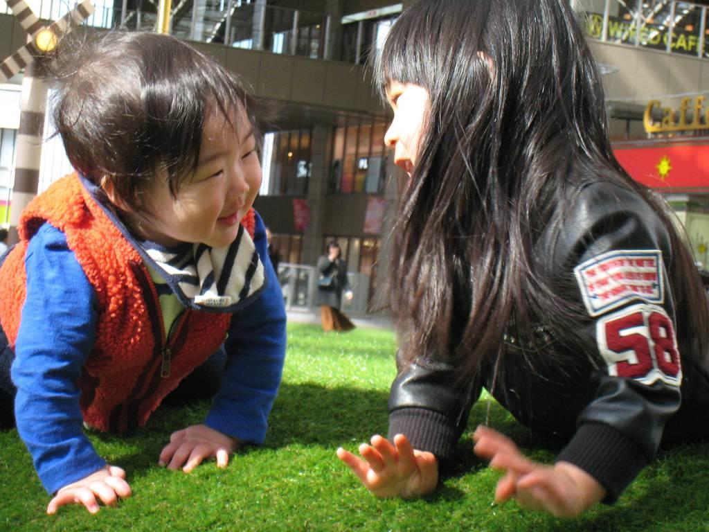 芝生広場で仲良く遊ぶ子供たち=大阪市北区の大阪駅