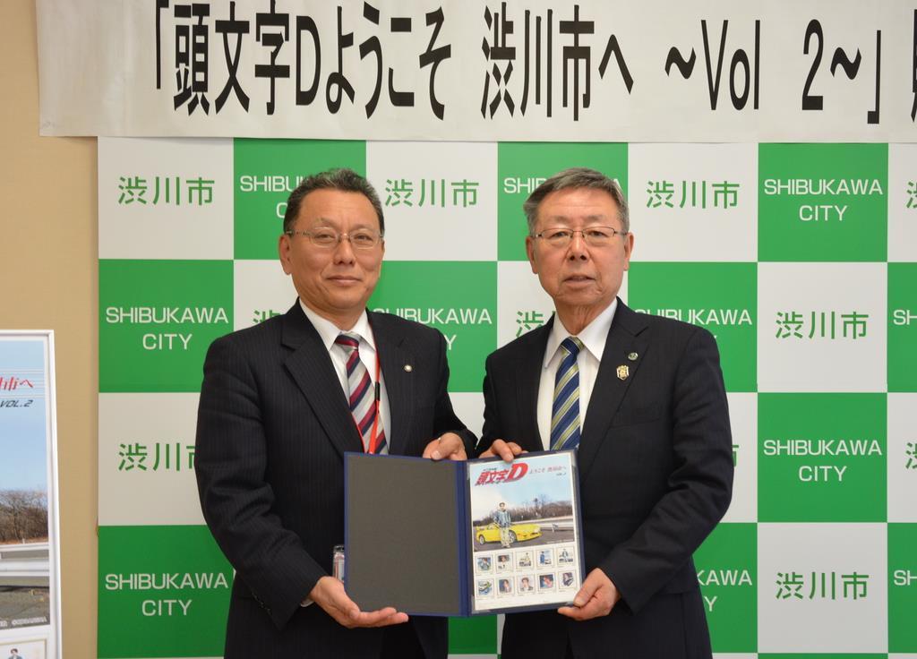 神保一雄群馬棟高郵便局長(左)から高木勉渋川市長に、オリジナルフレーム切手が贈呈された