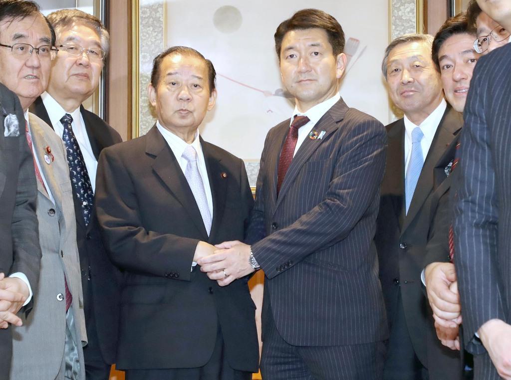 自民党から大阪市長選への出馬要請を受け、二階俊博幹事長(中央左)と握手する柳本顕氏=15日午後、東京・永田町の党本部(春名中撮影)