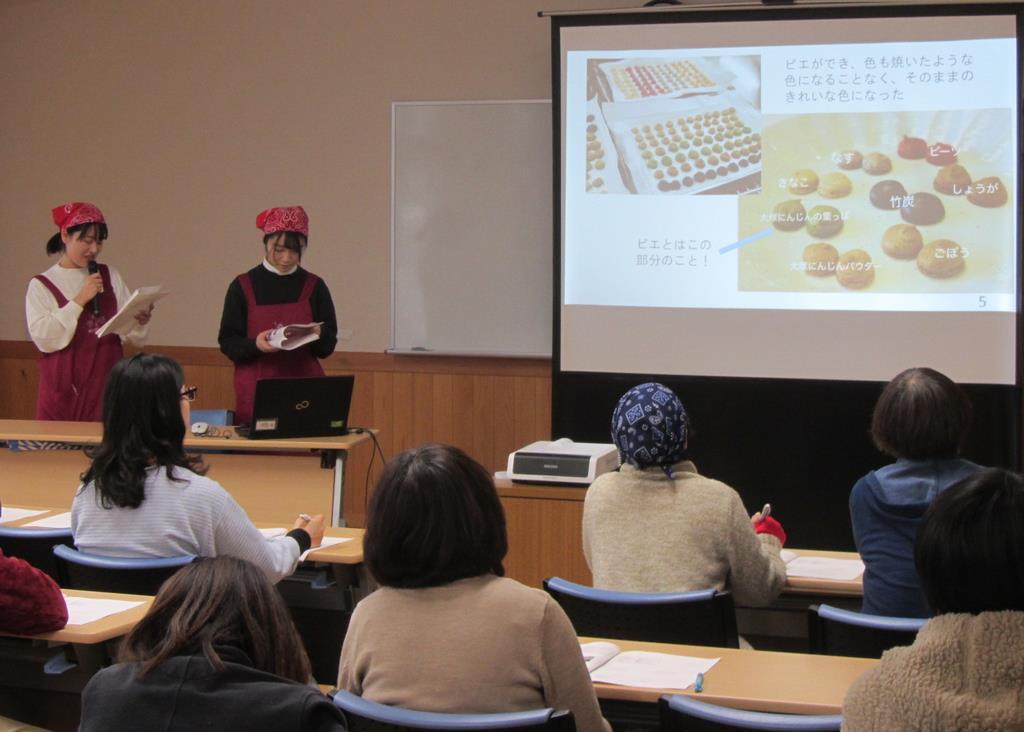 「大塚にんじん」などを使ったマカロンを説明する学生=2月28日、身延町下山(県提供)