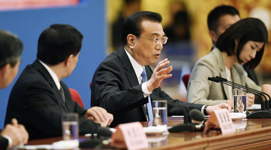 中国全人代が閉幕し、記者会見する李克強首相(中央)=15日、北京の人民大会堂(共同)